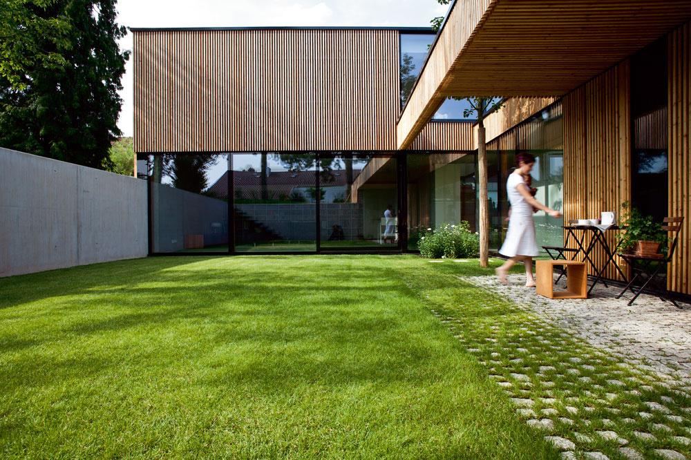 Čistá architektúra domu je založená na kompozícii jednoduchých geometrických objektov akontraste troch materiálov – štruktúrované plochy dreveného obkladu fasády sa striedajú sveľkými zaskleniami asivým povrchom pohľadového betónu.