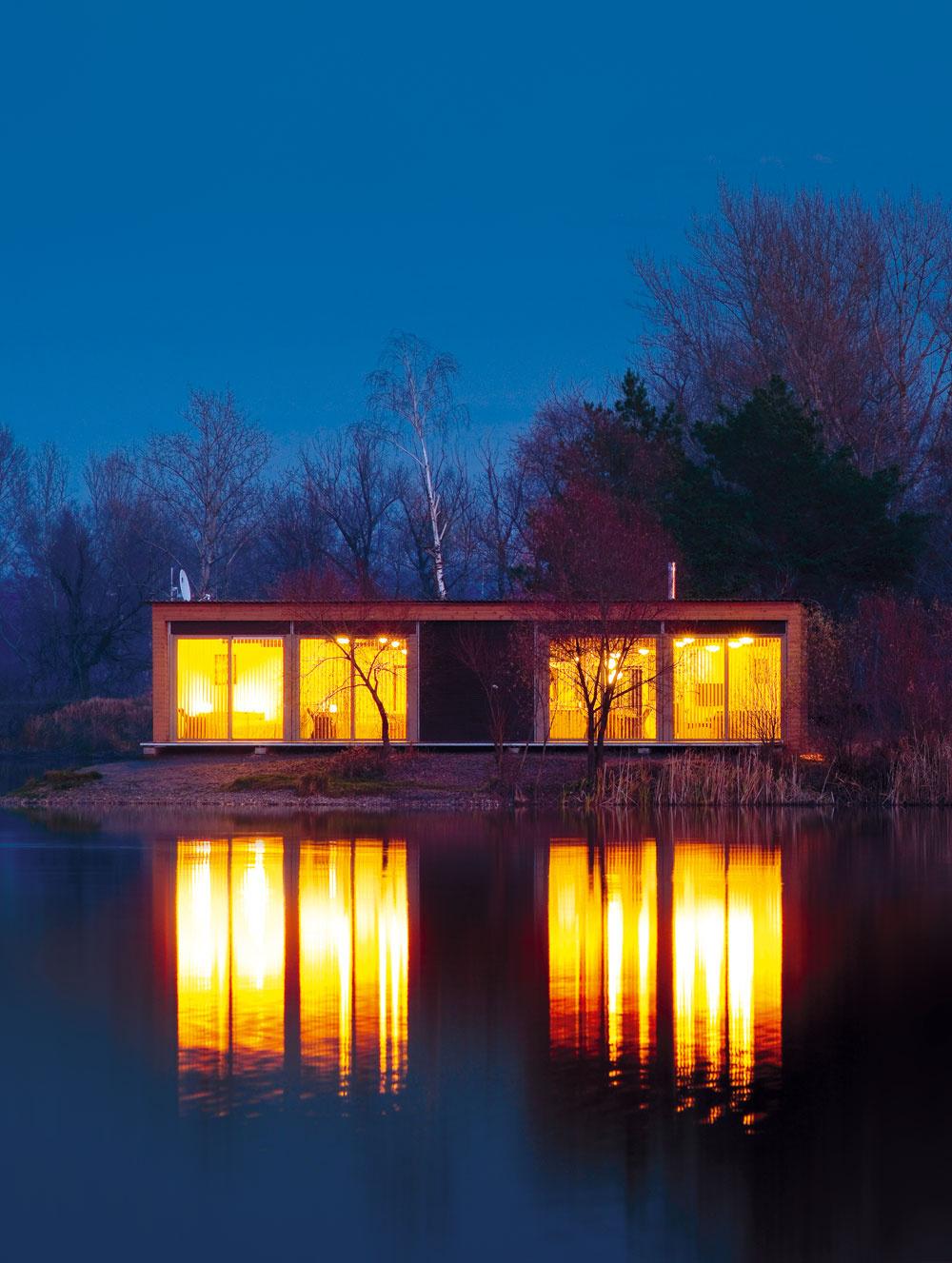 Zoči-voči chate, plaviac sa loďkou kostrovčekom alebo hľadiac zprotiľahlého brehu zistíte, že chata má aj vyhranenú tvár. Tabule zo skla vpúšťajú obrazy jazera do spální aobývačky. Večer sa cez zasklené priečelie leje svetlo chaty do vodných hlbín.