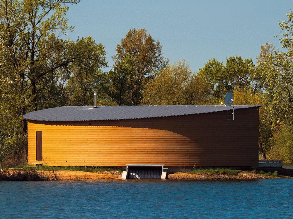 Jednoduchá forma a minimalistický koncept vyhovuje bezpečiu chaty. Vlnitý plech na pultovej streche odkazuje na vodnú hladinu
