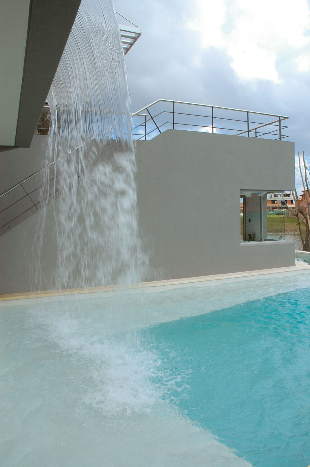 Široký prúd vody padajúci znádrže na prvom poschodí je nielen efektný, jeho šum tlmí okolitý ruch avoda ochladzuje bezprostredné okolie domu. Teplotu vody prispôsobuje elektronický systém teplote vzduchu.