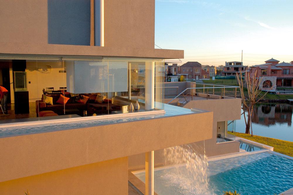 Takto sa dom javí zpohľadu najbližších susedov. Na nádrž na poschodí abazén nadväzuje bazénik pred spálňou, ktorej strešné okno vidieť na terase. Pekným detailom je nadväznosť technicistického oceľového komína na okrúhle piliere.