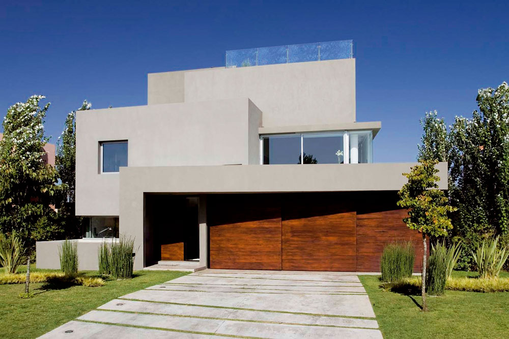 Priečelie je komponované ako séria štyroch prekrývajúcich sa plôch – posledná ohraničuje schodiskový priestor. Kompozíciu dopĺňajú dva lomené pásy – zadný nad oknom na poschodí je akoby slabým echom pásu lemujúceho vstup do domu a drevenú garážovú bránu. Nízke okno obývačky vytvára ilúziu, že je nad ním ďalšie poschodie.