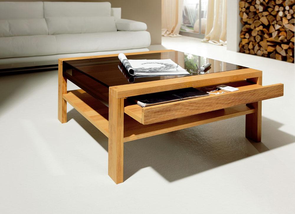 Konferenčný stolík Hülsta CT 120 spraktickou zásuvkou. Vyhotovenie: štruktúrovaný bukový masív, prírodný dubový masív asklo sbronzovým odtieňom. Rozmery: 70 × 70 × 42 cm. Cena od: 1 063€. Predáva Design House.
