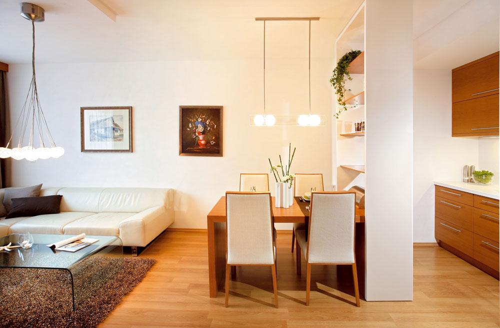 """Zjednocujúcim prvkom celého interiéru je použitie tíkovo morenej dubovej dyhy na nábytku vyrobenom na mieru a neutrálnych bielych prvkov,"""" vysvetľuje Marianna. """"V bytových priestoroch 2 + kk je častokrát nevyhnutné vyriešiť spojenie priestoru kuchyne a obývacej izby. V tomto byte sme na prianie majiteľky vizuálne oddelili kuchynskú časť od jedálne. Solitérna policová zostava je jednou z možností, ako dosiahnuť deliaci efekt a rozšíriť úložné priestory kuchynskej linky. Polica tvorí aj základňu pre rozkladací mechanizmus jedálenského stola. Môže zaň zasadnúť aj šesť osôb."""""""