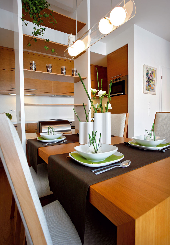 Linka v tvare L a odkladací priestor deliacej police príjemne a funkčne vymedzujú kuchynskú zónu. Deliacu policu doviezli vcelku. Zdvihli ju uprostred miestnosti, umiestnili na pomedzí jedálne a kuchyne, ukotvili do stropu. Solitérny kus nábytku je tak trochu komodou, detašovaným kuchynským pracoviskom a podávacím okienom na výdaj domácej stravy. Oceľou spevnené tenké odyhované poličky opticky odľahčujú masívnejší rám.