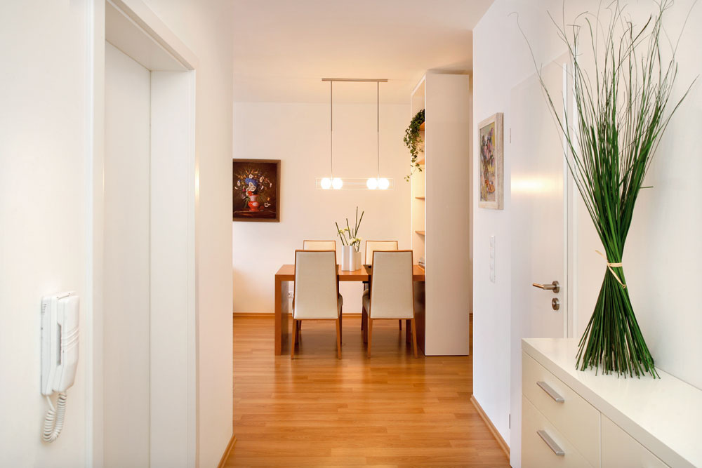 Priestor bytu sa príchodzím otvára hneď od vstupu. Návštevníka víta výhľad na zátišie s jedálenským stolom. Pomyslí si: to bude naisto prívetivá domácnosť.