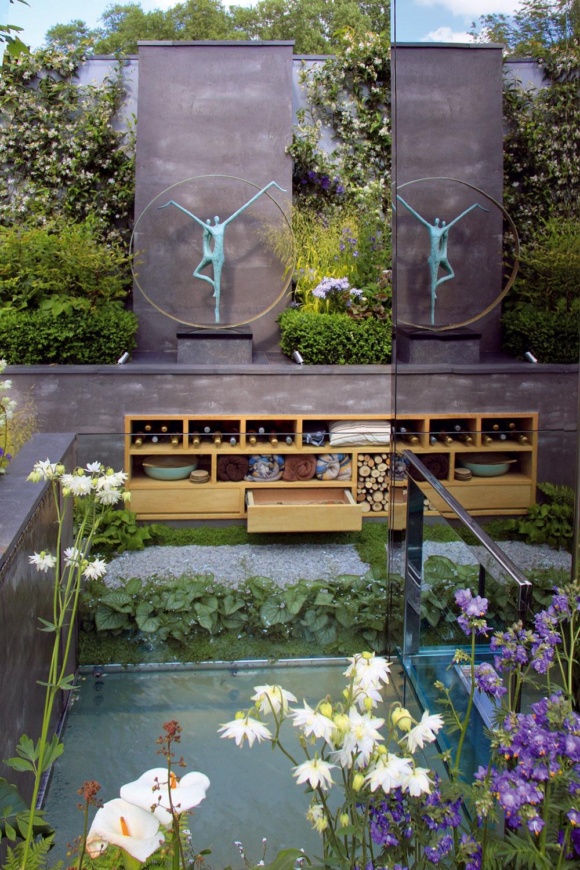 Pred kozubom je situovaná geometricky tvarovaná vodná nádrž, miesto si tu našla aj vkusná záhradná plastika – dar od rodinných známych.