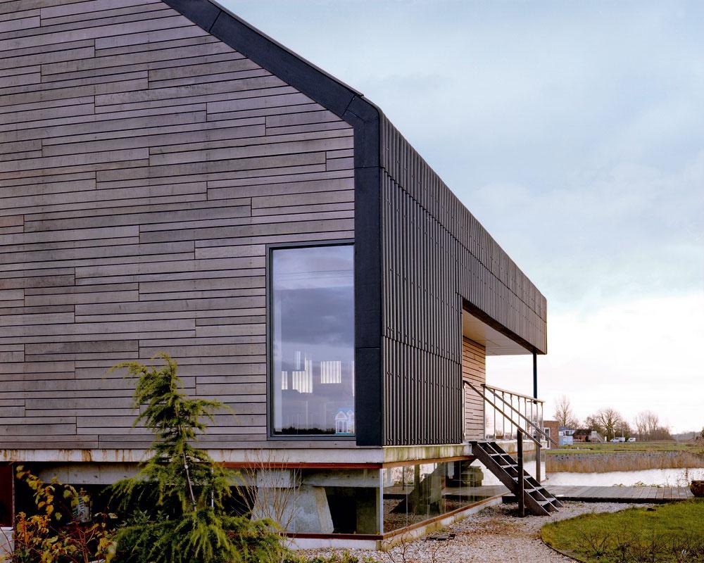 Plášť domu je takmer celý zantracitovo sfarbených platní vlnitého plechu. Na strategických miestach sú doň vsadené zasklené plochy tak, aby vinteriéri vznikol pocit intenzívneho prepojenia sokolitou krajinou, zdvihnutie hlavného obytného podlažia meter nad úroveň zeme tento vnem ešte zintenzívnilo. Štítové steny pokrýva svetlé drevo, ktoré pôsobí odľahčujúco.