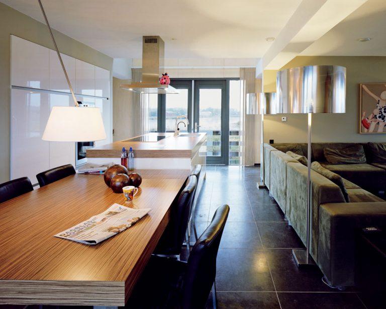 Takmer celé vyvýšené prízemie je venované jednej veľkej dennej miestnosti. Hoci dom pôsobí zvonka ako uzavretý, rafinovane komponované zasklenia, ktoré umožňujú priehľady naprieč domom avýhľady do krajiny okolo Groningenu, vytvárajú vinteriéri pocit otvorenosti aešte zintenzívňujú dojem veľkorysého priestoru.