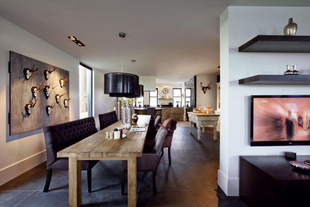 Jedálenský stôl so štruktúrovaným povrchom, zhotovený na objednávku zo starého dreva, je príkladom interiérových prvkov, ktoré vdome vytvárajú štýlovú ioptickú protiváhu geometrickým tvarom aneutrálnym hladkým povrchom. Do kuchyne sa vchádza spredu, cez vysoké sklené dvere; okolo starožitného kuchynského pracovného stola sa prechádza do osobitnej miestnosti na prípravu jedál.