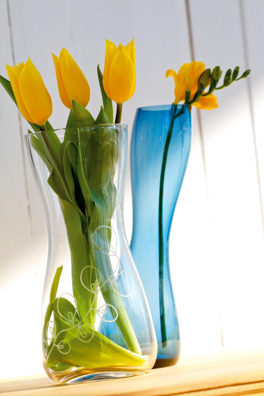 Váza Blomster zčíreho skla sbielym ornamentom. Dizajn PAmsell/B Wesslander. Výška 24 cm. Cena 6,99€. Predáva IKEA. Váza Beat zmodrého skla od firmy Leonardo. Výška 25 cm. Cena 19,82€. Predáva Galan.