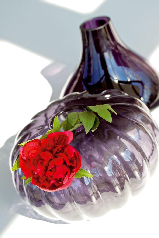 Váza Varlikt zručne fúkaného skla, ošetreného tónovaným lakom. Dizajn Gunnel Sahlin. Výška 16 cm. Cena 9,99 €. Predáva IKEA. Vpozadí váza Flux od firmy Leonardo. Výška 27 cm. Cena 90,22 €. Predáva Galan.