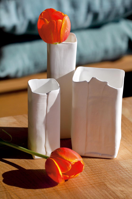 Tri biele vázičky od firmy Serax zkvalitného porcelánu Bone china sprímesou kostí, ktorá mu zabezpečuje mimoriadnu belosť apevnosť. Dizajn Roos van de Velde. Výška 12, 13, 16 a18 cm. Cenaod 8,80 €/kus. Predáva Bird&Tree.