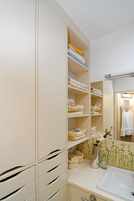 Aby sa neubralo na objeme kúpeľne, farby sú svetlé, svetlo jasné plnospektrálne. Miestnosť sa javí vyššia vďaka na mieru vyhotovenej policovej azásuvkovej nábytkovej stene.