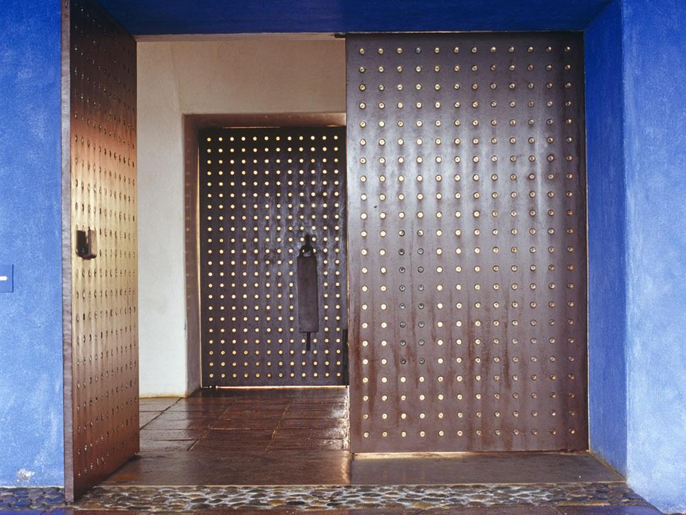 ntenzívne hutné farby obopli steny domu, sebavedome vstúpili na terasy, podstrešie, nasťahovali sa do patia, rozžiarili haciendu terakotovou červeňou, okrovou žltou amajestátne modrou. Omodré ostenie sa zavesili krídla prvých oceľových dverí. Pravidelne usporiadané kruhové otvorčeky sintarzovaným sklom umocnili sminimalistickou manierou už aj tak veľkolepý dojem zdvojo za sebou zoradených vstupných dverí. Architekt sa vtomto prípade inšpiroval arabským štýlom navrhovania vstupov do bohatých domov.