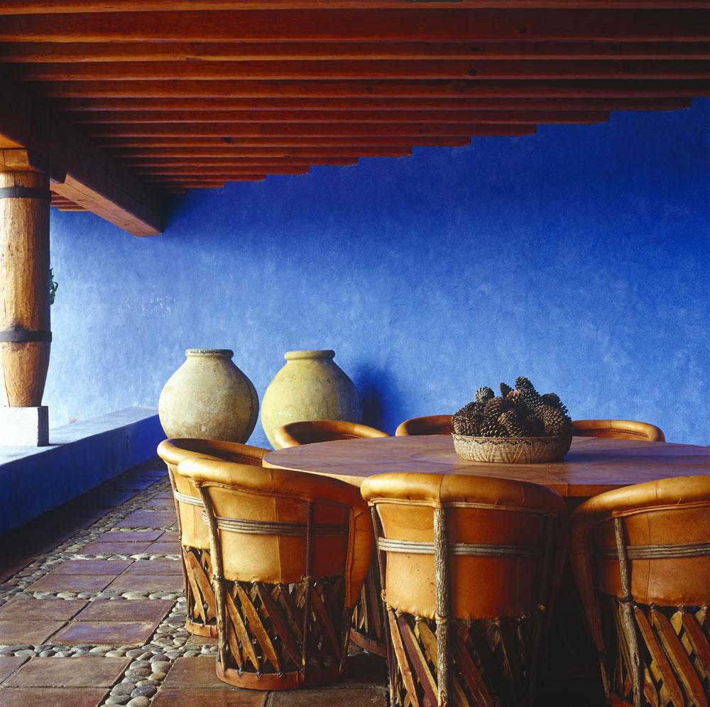 Objemné keramické nádoby strážia rozmernú verandu haciendy, ukryté pod mohutným previsom strechy. Voľakedy vnich dovážali olivový olej alebo iný, vtedy vtýchto končinách nedostatkový tovar vpodpalubí korábov, ktoré sa plavili zo starého kontinentu. Drevené trámy strešnej konštrukcie amasívne stĺpy pripomínajú architektonické tradície koloniálnych čias. Architekt José de Yturbe nasledoval myšlienku vytvárania veľkých navzájom sa prelínajúcich objemov, ktorých dojem umocňujú majestátne farebné plochy. Výrazná farebnosť prežiarená mexickým slnkom je natoľko emotívna, že sa pokojne zaobíde bez ďalšej dekoratívnosti. Vpríjemnom kontraste avnevyhnutnom množstve sa tu zariaďovalo masívnym dreveným nábytkom vkoloniálnom duchu. Podlahy chladí achráni kamenná dlažba, ktorá si miesto na dlážke vpravidelných intervaloch rozdelila spásmi vyskladanými zriečnych okrúhliakov.