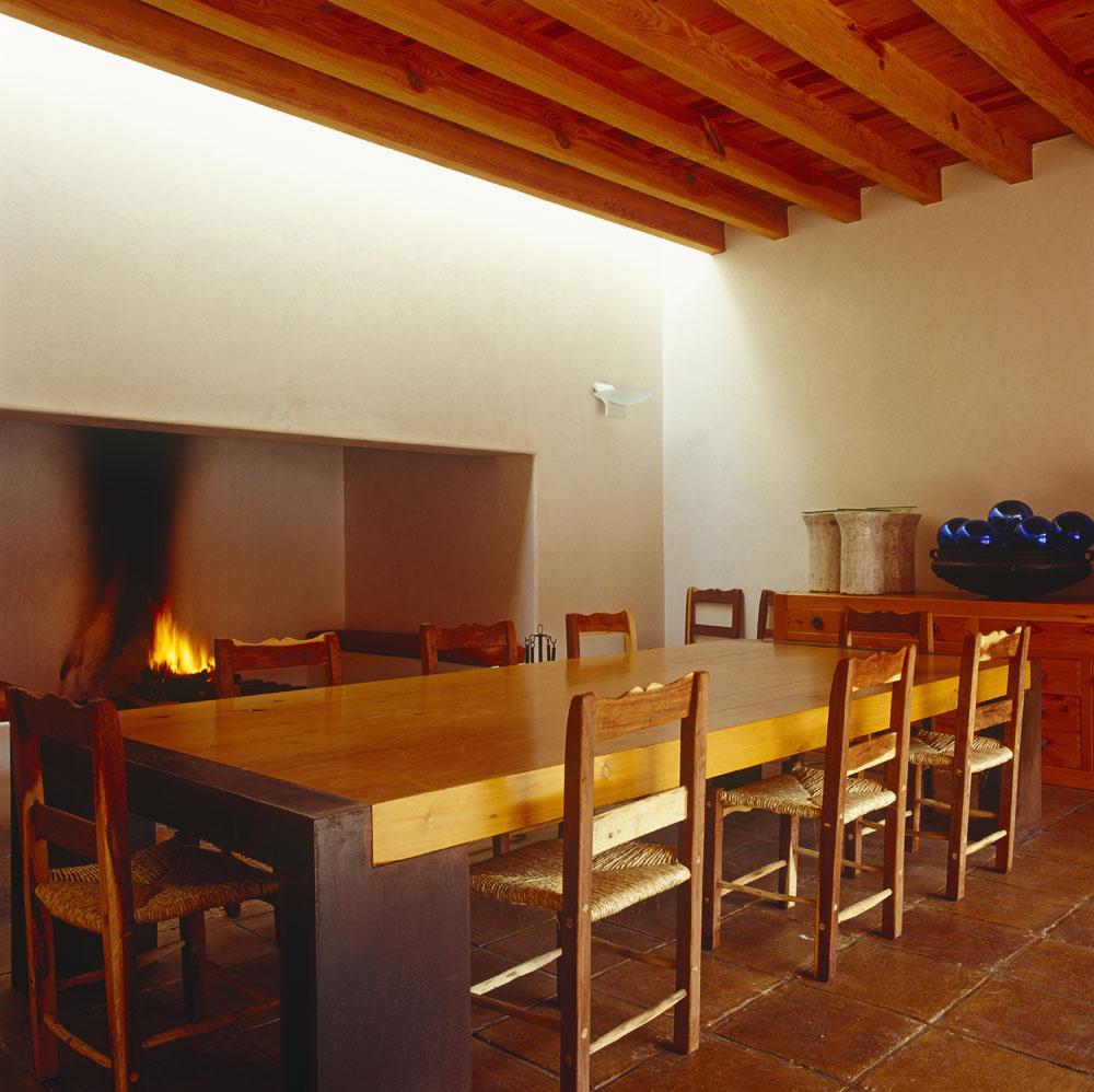 """Rustikálne pohodlie za minimalisticky """"vystrihnutým"""" stolom. Masívny stôl získal formu vďaka návrhu architekta domu. Jedáleň ajedálenský stôl majú byť predsa solídne ako staré rodinné väzby. Oheň plápolá vhlbokom aširokom výklenku kozuba, strop zosilnili drevené trámy, podlahu pokryla terakotová dlažba. Nečakaný je však nádherný prúd svetla, ktorý sa vydal dole stenou vústrety ohnisku."""