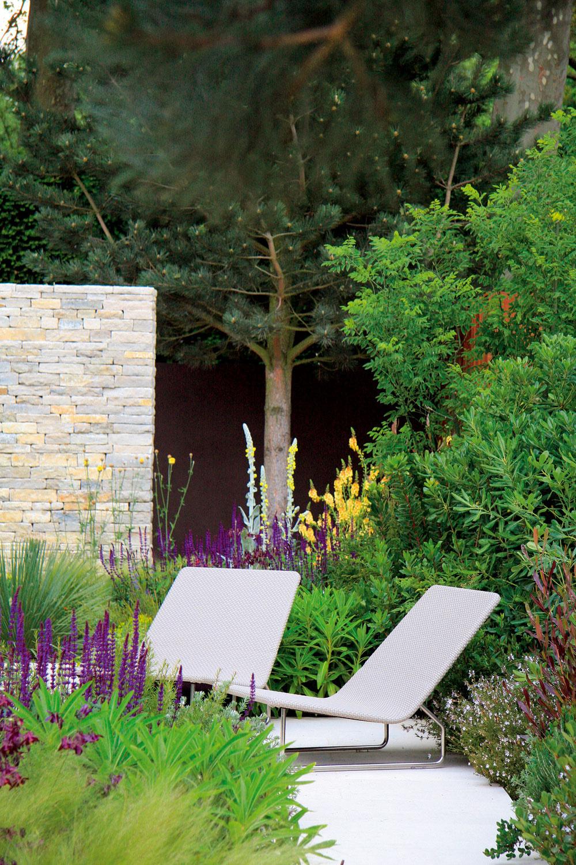 Kamenné apomerne vysoké múry vymedzujú priestor na stolovanie arelax. Vtieni stromov si na vydláždenej ploche domáci rozmiestnili exteriérový nábytok.