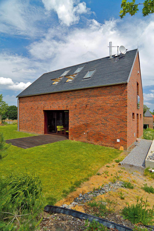 Bridlicová strecha dotvára výtvarný vzhľad tehlovej fasády. Vprírodnej téme pokračujú aj drevené terasy aokolitá zeleň.