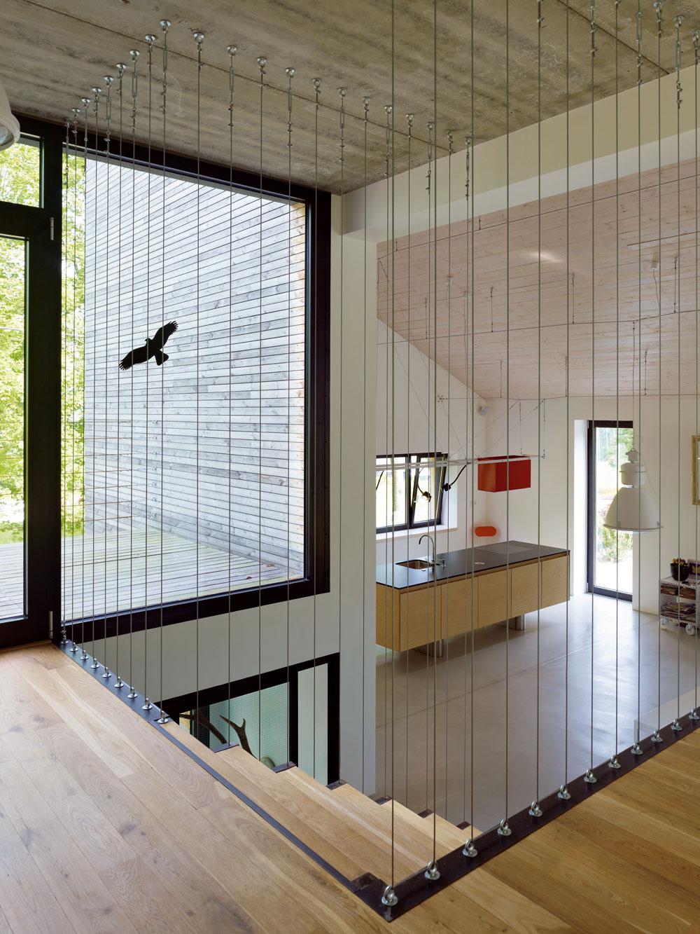 Vzdušný priestor nechceli zabiť masívnym zábradlím. Betónový strop je terčom kritiky mamy – architektky, ale domáci naň nedajú dopustiť. Páči sa im, ako si rozumie sdrevenými akovovými doplnkami.