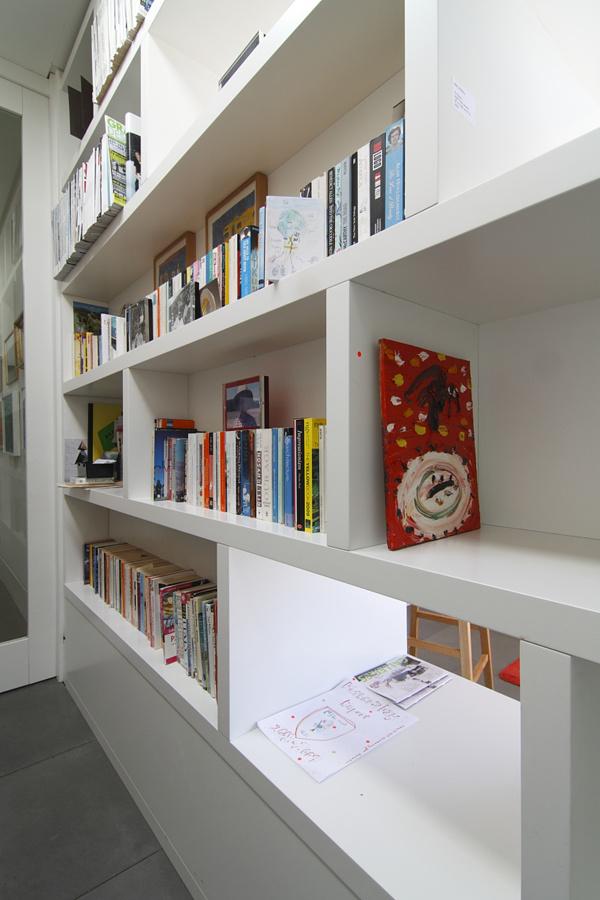 Metamorfóza deliacej priečky na knižnicu má nielen praktický význam. Stáva sa dekoratívnym prvkom konzervatívnej bielej steny.