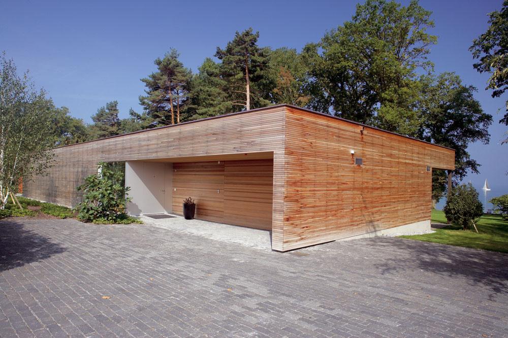 Zopačnej, južnej strany chráni súkromie interiéru drevom obložená stena. Odtiaľto sa vchádza do garáže aj do domu cez vstup prekrytý presahom strechy. Od cyklistického chodníka oddeľuje dom bukový živý plot.
