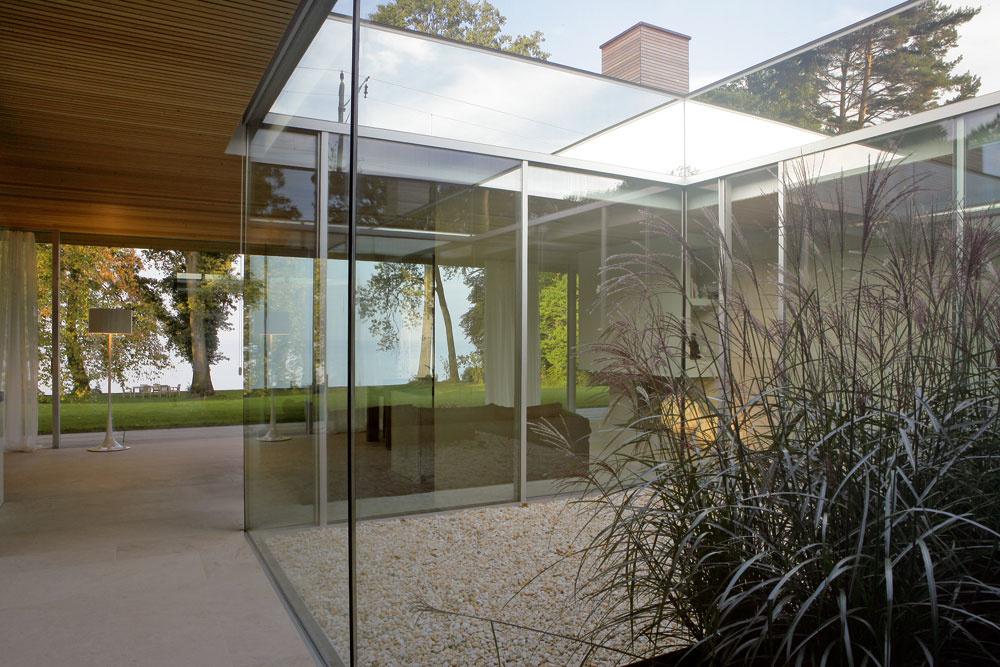 Centrálne átrium je akýmsi lapačom slnečných lúčov – pomáhajú mu vtom aj zrkadlá, ktorými je tu obložený okraj strechy. Vďaka skleneným stenám sa už po pár krokoch otvorí návštevníkovi pohľad naprieč celým domom až na Bodamské jazero.