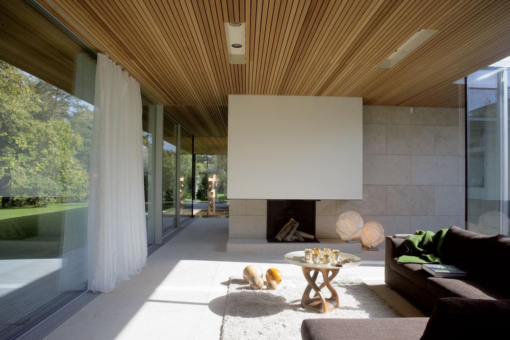 Vobývačke si môžete transparentnosť domu užiť naplno – na jednej strane sklenená severná fasáda svýhľadom, na druhej sklené steny slnečného átria. (Sedačka značky Flexform, stôl akoberec od spoločnosti Redbox, za stenou skozubom je otvorená spálňa.)