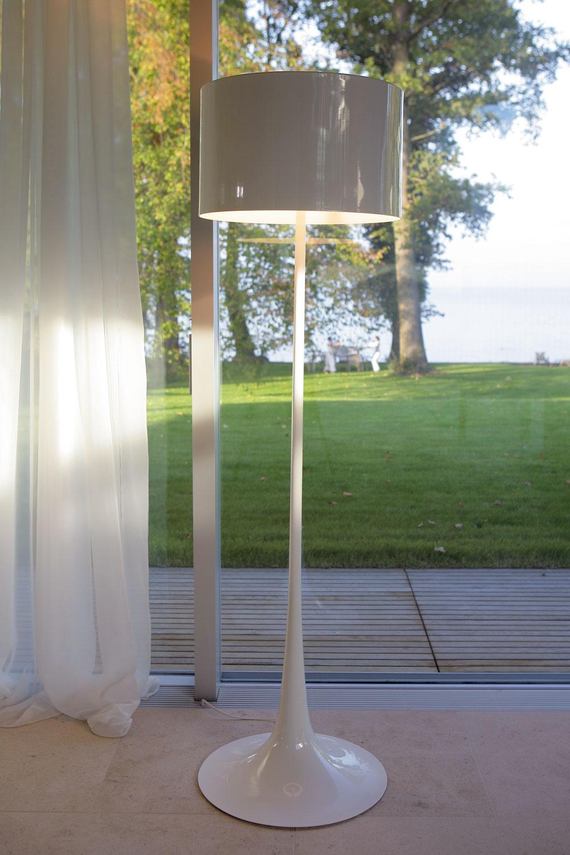 Na opačnej strane (oproti spálni) naznačuje hranicu medzi obývačkou akuchyňou lampa od firmy Flos. Posuvné sklenené dvere si dali vyrobiť na objednávku, svetlý kameň na podlahe pochádza zBurgundska.