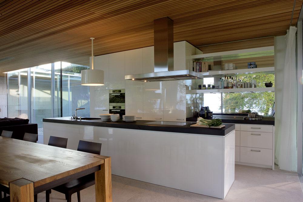 Rovnako ako sám dom, aj jeho zariadenie je premyslene jednoduché, elegantné čistými líniami apríjemné prírodnými materiálmi. Vďaka veľkému zrkadlu sa jazero aokolitá zeleň nasťahovali až do kuchyne.