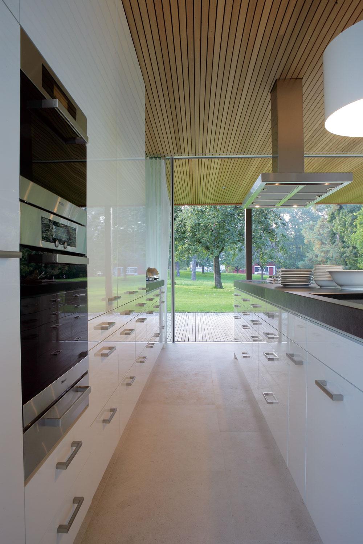 Kuchyňu slesklými dvierkami akontrastnou pracovnou plochou navrhol architekt Andreas Zech – zrovnakých bielych skriniek je vytvorená zadná stena aj varný ostrov. Hranatému antikorovému digestoru pôvabne kontruje oblá biela lampa nad drezom.