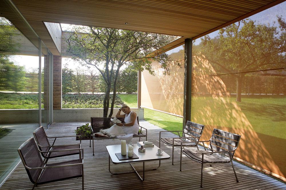 Pomocou hrdzavočervených roliet sa dá na Dvore pod stromom vytvoriť intímny priestor, chránený pred popoludňajším slnkom. (Záhradný nábytok Corex od firmy Ginkgo.)