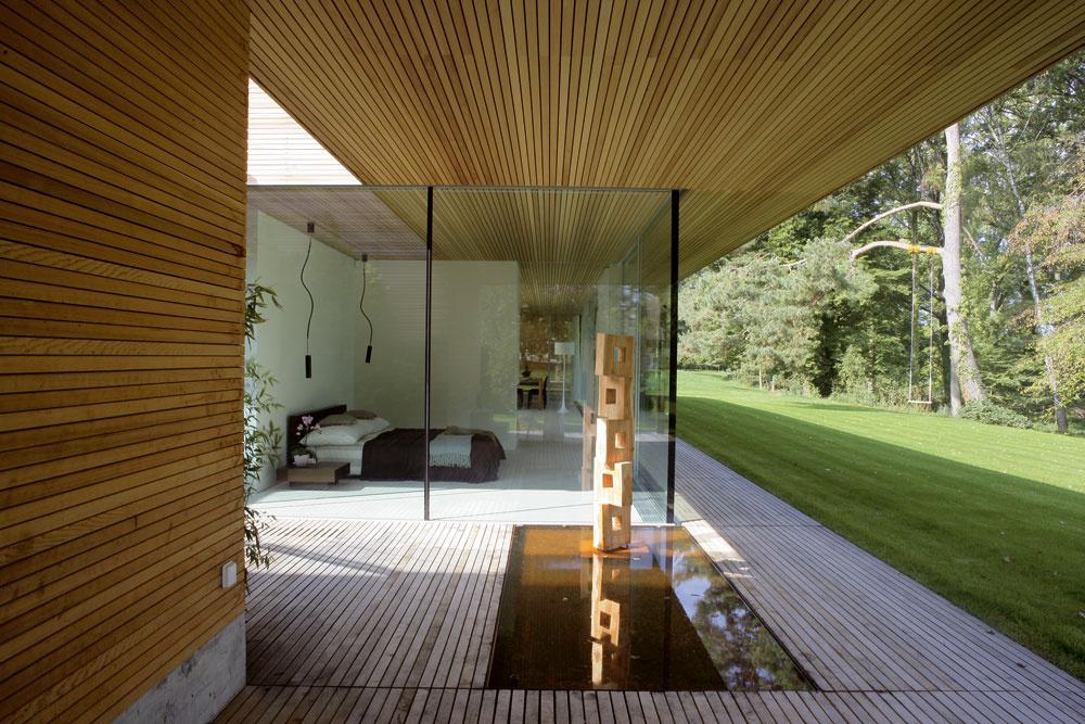 Elegantný aotvorený, apritom bezpečne chrániaci súkromie, plný slnka asnádherným výhľadom – aj keď veľký pozemok vyzeral idylicky, využiť naplno danosti nádherného miesta anaplniť predstavy jeho budúcich obyvateľov nebolo také jednoduché. Riešením architekta Zecha bol rafinovane transparentný dom, vktorom exteriér prerastá interiérom avnútorné priestory plynulo prechádzajú do vonkajších.