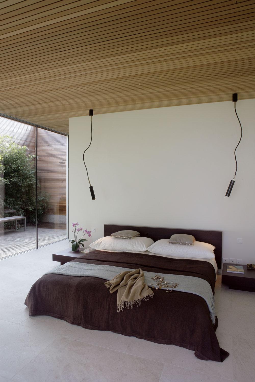 Východná časť domu je vyhradená spálni asúkromnému zázemiu. Posteľ anočné stolíky zwenge navrhol architekt, lampy sú od firmy Santa & Cole.