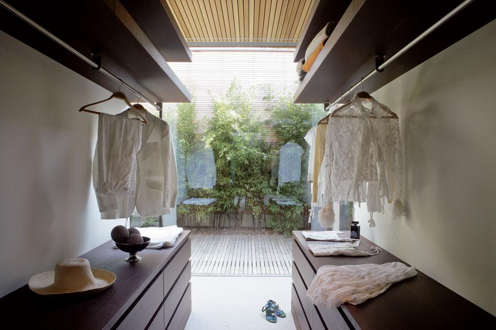 Šatníku – obliekarni ztmavého dreva wenge – pripadlo logické miesto medzi spálňou akúpeľňou. Aj zneho je cez sklenenú stenu výhľad na Kúpací dvor.