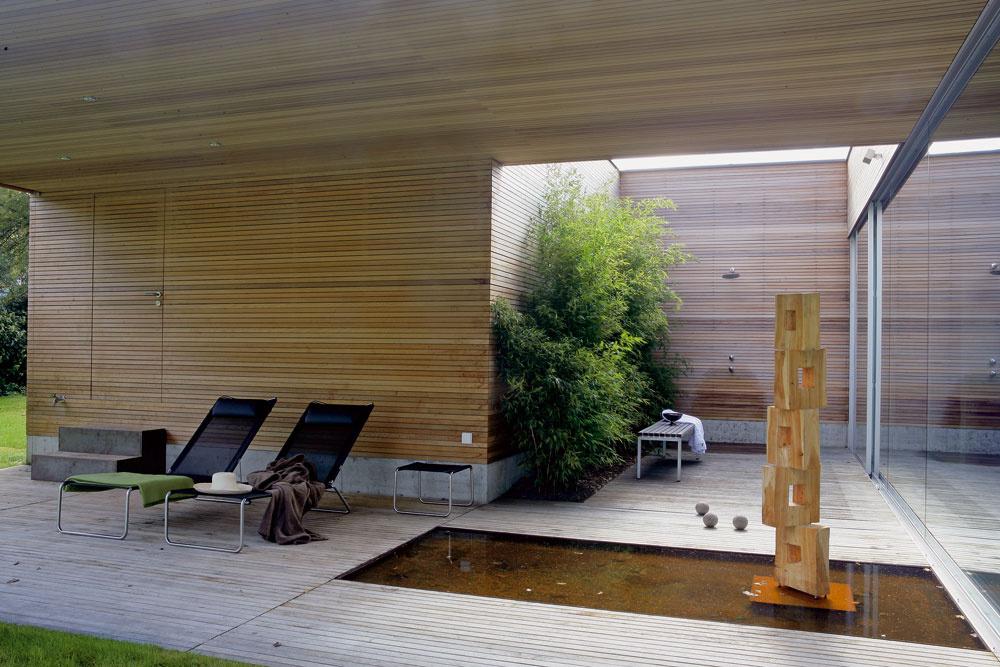Cez tri výrezy vstreche nad troma exteriérovými priestormi, začlenenými do dispozície, sa architektovi podarilo priviesť do domu svetlo aj zjužnej strany – vonkajší priestor na východnom konci domu pred spálňami je intímnou zónou oddychu. Majiteľ aarchitekt mu dali názov Kúpací dvor. (Ležadlá sú od firmy Ginkgo, drevenú plastiku navrhol stavebník.)