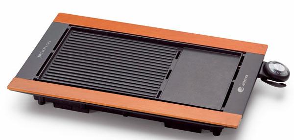 Stolový gril Fagor BBC-850, dizajn s dreveným zakončením, jedna strana vrúbkovaná, druhá hladká s nepriľnavým povrchom, tepelne izolovaná rukoväte, príkon 2 500 W, súčasťou je podnos na odkvapkávajúci tuk, vhodný do umývačiek riadu, rozmontovateľný na ľahké čistenie, výhodou je veľká plocha na pečenie (52,8 × 29,3 cm, kontrolka termostatu a tlačidlo regulácie teploty s piatimi polohami, možnosť servírovania priamo na doske. Odporúčaná cena 129 €.