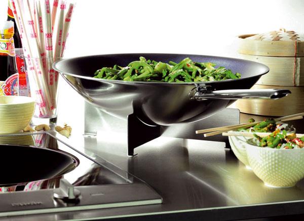 Indukčný wok od firmy Miele spanvicou wok, ktorá sa umiestni vpriehlbine sklokeramickej plochy. Zaručuje sa tak bezprostredný prenos tepla na pokrmy. Pripojiteľný Booster dodá extra výkon. Rozmery 38 × 52 cm. Cena 1 961 €.