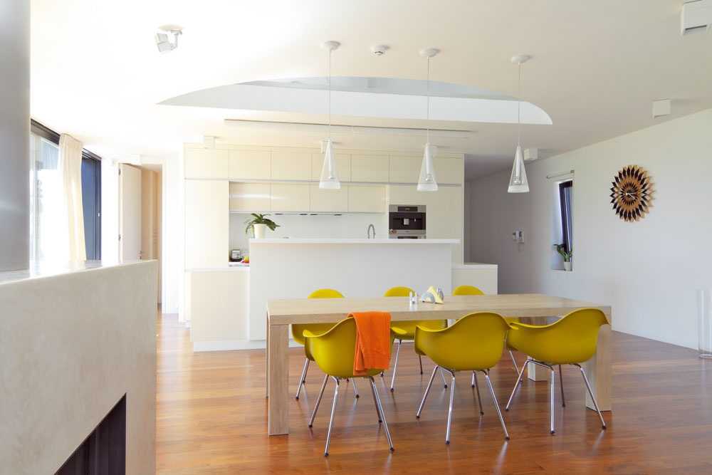Striedmu farebnosť osviežujú pestré doplnky. Bielu kuchyňu sjedálenskou zónou rozpumpovali žlté stoličky. Nad kuchynským ostrovčekom vidieť časť kruhového pôdorysu pracovne.