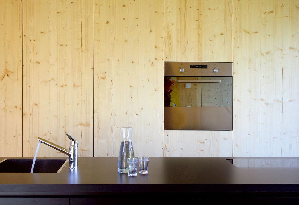 Čierna farba si našla miesto aj vinteriéri. Okrem dlažby na celom prízemí sa vprípade kuchyne uplatnila tiež na ostrovčeku. Za drevenou stenou sú ukryté všetky potrebné odkladacie priestory azabudované spotrebiče.
