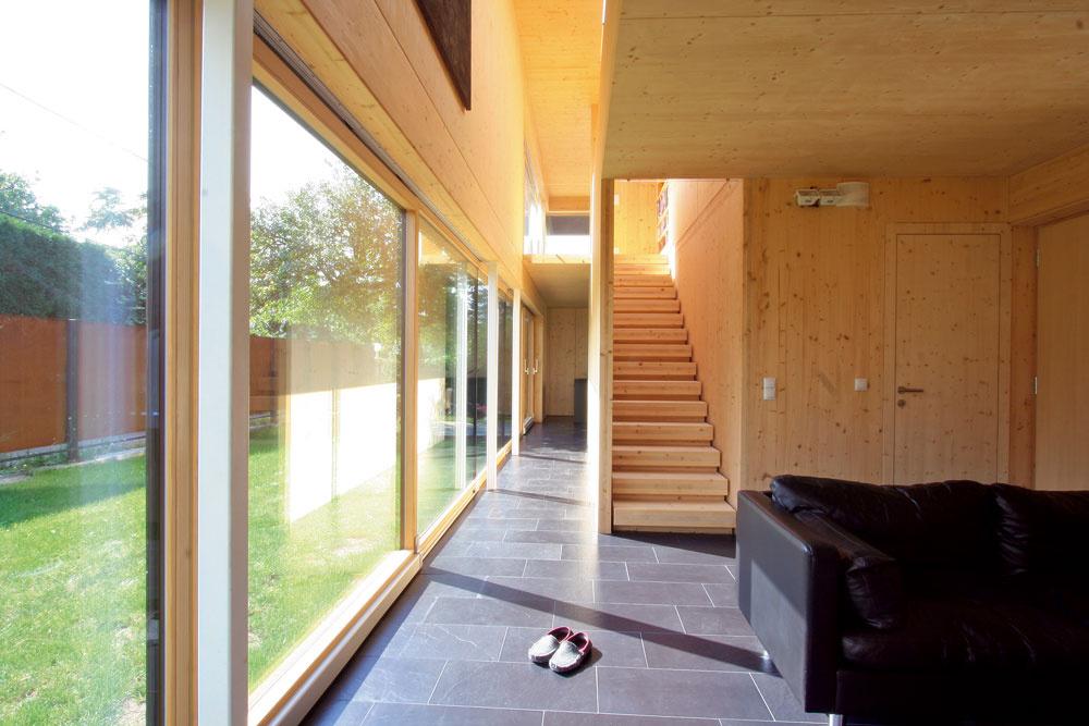 """Zobývačky vedie drevené schodisko na poschodie, okolo neho sa chodbou popri južnej zasklenej fasáde prechádza do kuchyne. Prostredníctvom galérie je vtejto časti čistý asvetlý priestor obývačky ešte viac otvorený aprepojený spracovňou na poschodí. Posuvné zasklené steny tvorili vrozpočte podstatnú položku, vďaka úsporám pri fasáde si však mohli Günter aRita tento """"špás"""" dovoliť."""