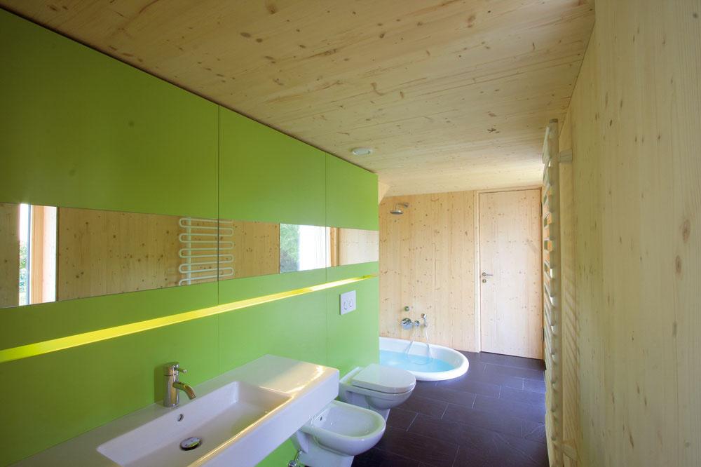 Kúpeľňa je prístupná veľmi prakticky – ako zo vstupného priestoru, tak aj zkuchyne, nie je však priechodná. Každodenná komunikácia je vyriešená okolo nej, popri sklenenej záhradnej fasáde.