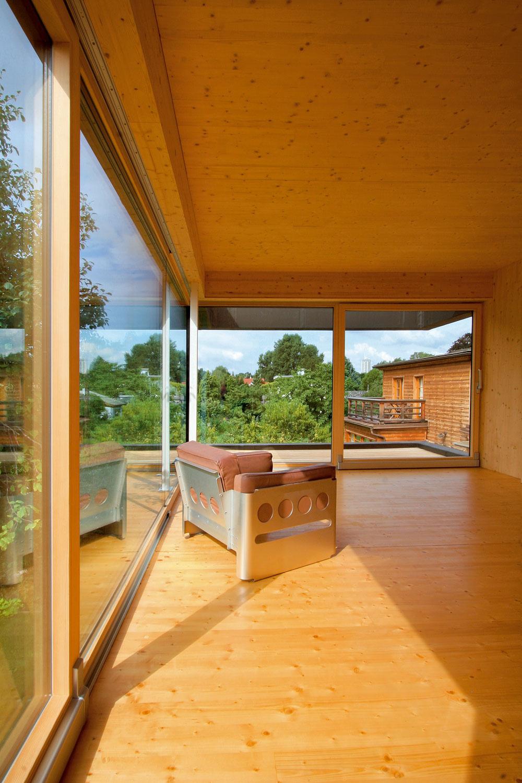 Svetlo aotvorený priestor sú charakteristickými znakmi celého domu. Čisté, otvorené aminimálne členené interiéry pôsobia priestrannejšie anechávajú vyznieť krásu dreva. Väčšie než vskutočnosti vyzerajú aj vďaka jeho svetlému odtieňu atiež zásluhou veľkých zasklených stien orientovaných na všetky svetové strany, ktoré dožičia obyvateľom dostatok svetla, ale najmä výhľady akontakt sterasami azáhradou. (Pohľad zpracovne smerom kterase pri spálni. Dnes je už spálňa zariadená posteľou anočnými stolíkmi.)