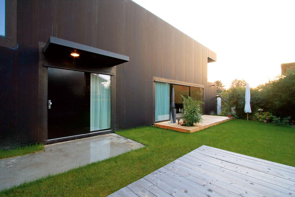Severná fasáda so vstupnými dverami po daždi, osvetlená zapadajúcim slnkom. Záhradnú terasu sfontánkou umiestnil architekt Pichler vnadväznosti na kuchyňu ajedáleň.