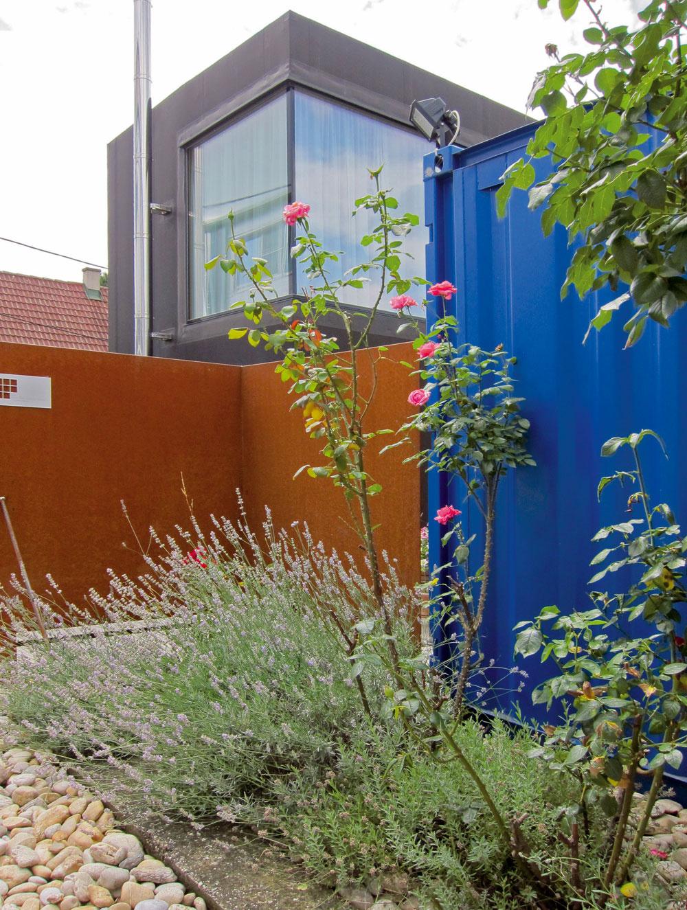 VRakúsku je zvykom oddeľovať záhradkárske oblasti od zvyšku mesta oplotením avo vnútri zóny ich pospájať sieťou súkromných uličiek. Stavbu na nárožnom pozemku chráni od ulice kovový plot so skorodovaným povrchom, ktorý svojou farebnosťou zaujímavo kontrastuje sjej čiernou fasádou. Keďže veľkú časť južného priečelia tvorí na prízemí zasklená stena, plné tabule oplotenia mali poskytnúť pocit intimity jednak vzáhrade, jednak vdome.