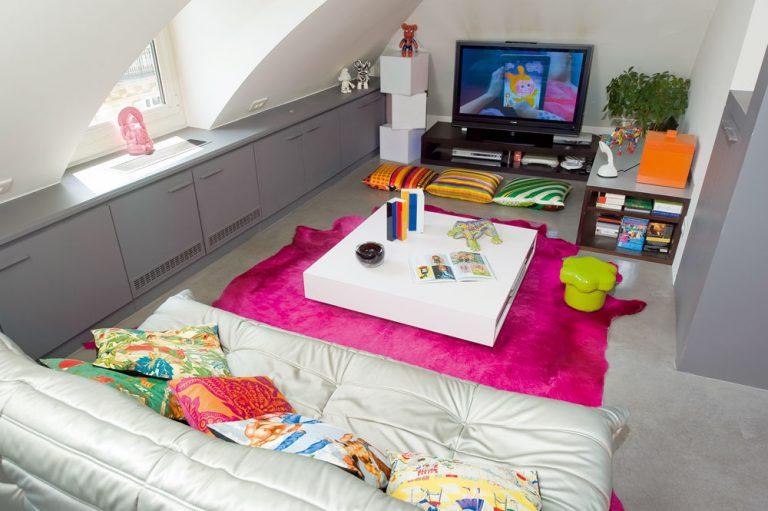Neutrálny podklad, na ktorom skvele vynikne farebný nábytok aj doplnky, vytvorili biele steny ahladká sivá dlážka – pôvodné staromódne linoleum aklasickú terakotovú dlažbu nahradila vcelom byte liata betónová podlaha, ošetrená voskom. Vobývačke ju oživuje najmä fuksiovo ružový koberec zhovädzej kože apestrofarebné vankúše – keďže obývačka nemá všade dostatočnú výšku, sedí aj býva sa tu čo najviac pri zemi. Najnižšiu časť obývacej izby pri obvodových stenách prakticky využili sivé skrinky vyrobené na mieru.