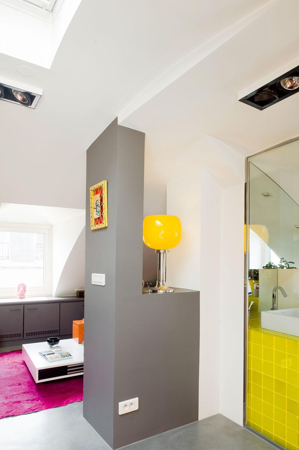 Časť nosnej steny, natretá sivou farbou, vytvára hranicu medzi rôznofarebnými svetmi kúpeľne, kuchyne aobývačky. Elegantne pritom ladí sbetónovou podlahou aneutrálne sivými skrinkami vobývacej izbe.