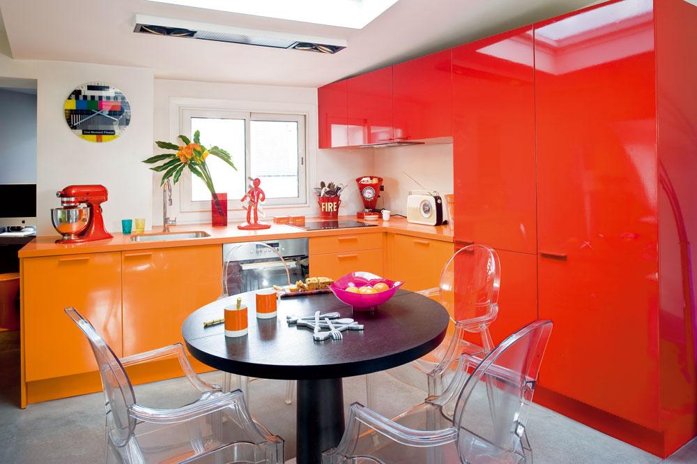 Kuchynská linka vtvare L je vyskladaná zbežných sektorových skriniek zIkey (séria Applad). Ich pôvodný povrch však dali ustolára natrieť akrylátovou farbou analakovať. Oranžové ačervené skrinky lemujú jedálenský stôl ztmavého dreva (starší model od značky Cinna), doplnený stoličkami zpriehľadného polykarbonátu. Známe stoličky Louis Ghost, ktoré pre firmu Kartell navrhol Philippe Starck, dizajnéri milujú pre rafinovanú kombináciu klasického tvaru apriam éterického materiálu, ktorý nezaťaží ani malý priestor. Doplnky uložené na pracovnej doske zoranžového Corianu sú zladené sdominantnou vysokou červenou skriňou – od kuchynského robota Kitchen Aid cez stojan na nože Voodoo od La Chaise Longue až po zmenšeninu červeného hasičského vedra, ktorá slúži na uloženie príborov aďalšieho riadu.