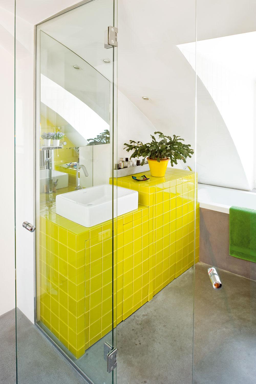 Jednotná hladká podlaha anenápadné steny pomohli zjednotiť aopticky zväčšiť pomerne malý akomplikovane členitý priestor, jasné farby dodali každej funkčnej zóne vlastnú identitu. Kúpeľňu oživenú sviežim odtieňom citrusov otvoril architekt do kuchyne aaj vďaka svojej farbe perfektne zapadla do denného obytného celku.