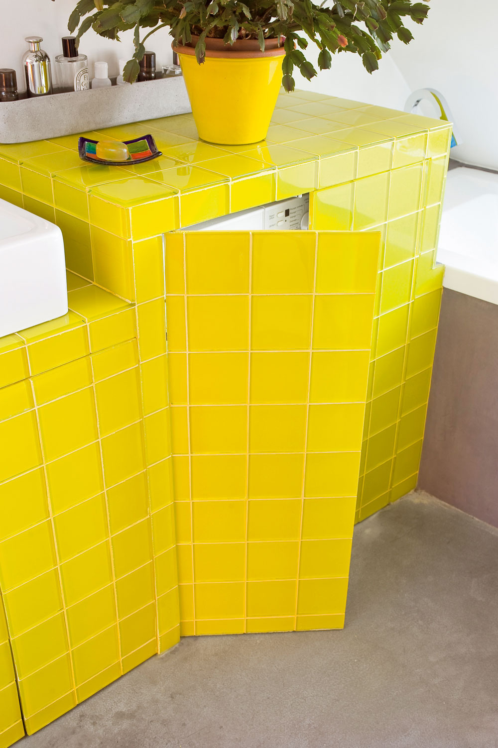 Každej miestnosti dodáva charakteristickú farebnosť len zopár kúskov vybavenia, zvyšok je neutrálny, sivo-čierno-biely. Do kúpeľne priniesol architekt farbu najmä prostredníctvom hranatého objektu sumývadlom – skrinka so sadrokartónovými stenami acitrónovožltým skleneným obkladom (formát 10 × 10 cm od Aire Azur Carrelage) ukrýva práčku akôš na špinavú bielizeň. Aj pri špinavej bielizni, našťastie, funguje porekadlo Zíde zočí, zíde zmysle.